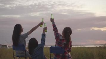 Asian woman sitting on a chair with friends drinking beer video