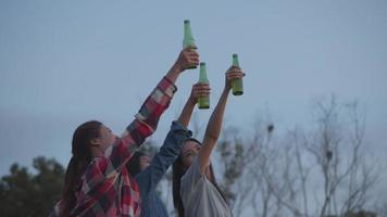 Asian women celebrate among friends, camping and drinking beer video