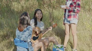 Asian woman playing guitar while camping with friends video