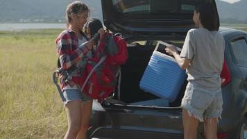 femmes asiatiques prenant des sacs à dos et des glacières de la voiture video