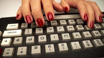 A vintage computer keyboard with the hands of a woman typing video