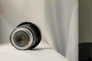 Lente de zoom de cámara negra sobre tela blanca foto