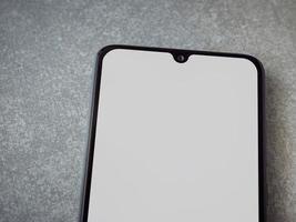 La maqueta de teléfono inteligente móvil negro se encuentra en la superficie con una pantalla en blanco aislada sobre un fondo de piedra cerámica de granito de porcelana foto