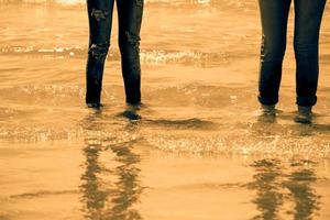 Women legs in blue jeans standing in the sea water on the coast - golden tone photo