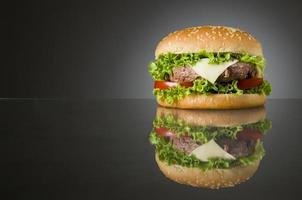 Delicious hamburger on black background photo