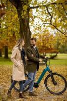 Young couple in the autumn park with electrical bicycle photo