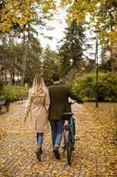 Rear view at young couple in the autumn park with electrical bicycle photo