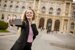 Young female tourist taking selfie with mobile photo in centre of Vienna, Austria