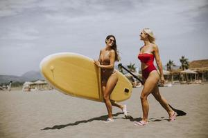 Two young women with paddle board on the beach on a summer day photo