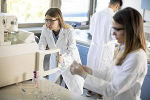 Female scientists in a white lab coat putting vial with a sample for an analysis on a ionchromatography system in biomedical lab photo