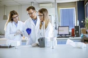Researchers in protective workwear standing in the laboratory and analyzing liquid samples at ion chromatography equipment photo
