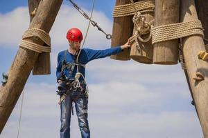 Extreme professional videographer during shooting on climbing tower working under extreme conditions photo