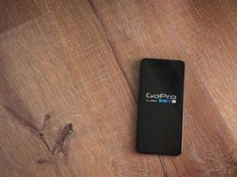 GoPro - Video Editor and Movie Maker app launch screen with logo on the display of a black mobile smartphone on wooden background photo