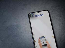 Quizlet - Language learning app launch screen with logo on the display of a black mobile smartphone on a dark marble stone background photo