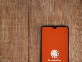 AccuWeather app launch screen with logo on the display of a black mobile smartphone on wooden background photo