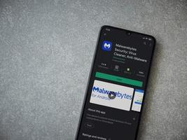 Malwarebytes Security app play store page on the display of a black mobile smartphone on ceramic stone background photo