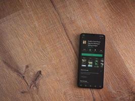Eyeem: aplicación para compartir y vender imágenes, página de Play Store en la pantalla de un teléfono inteligente móvil negro sobre fondo de madera foto