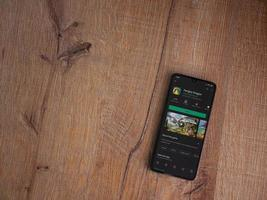 Hungry Dragon app play store page on the display of a black mobile smartphone on wooden background photo