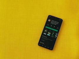 eyeem: aplicación para compartir y vender imágenes, página de Play Store en la pantalla de un teléfono inteligente móvil negro sobre un fondo de tela amarilla foto