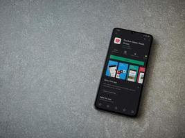 Pocket app play store page on the display of a black mobile smartphone on ceramic stone background photo