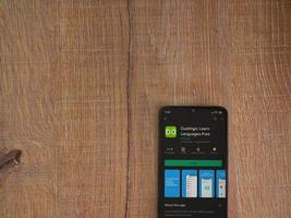 Duolingo - Language learning app play store page on the display of a black mobile smartphone on wooden background photo