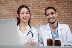 equipo de socios de atención médica, retrato de dos jóvenes médicos de etnia asiática con camisas blancas con estetoscopio, sonriendo y mirando a cámara en la clínica, personas con experiencia en tratamiento profesional. foto