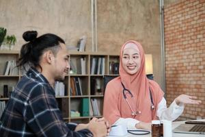 Young beautiful woman doctor is health examining male patient in office of hospital clinic and advising with a smile on medicines. This Asian medical specialist is an Islamic person wearing a hijab. photo