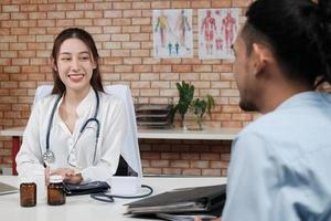 Beautiful woman doctor in white shirt who is Asian person with stethoscope is health examining male patient in brick wall background medical clinic, smiling advising medical specialist occupation. photo