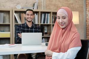 Portrait of entrepreneur of business startup, young male and beautiful female owner, two partners Islamic people, looking at camera, arm crossed and happy smiles in small e-commerce workplace office. photo