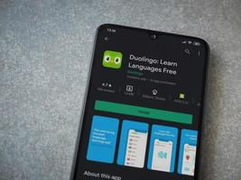 Duolingo - Language learning app play store page on the display of a black mobile smartphone on ceramic stone background photo