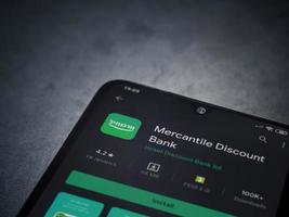 Bank Mercantil Discount app play store page on the display of a black mobile smartphone on dark marble stone background photo