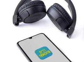 Black mobile smartphone with Radius 100FM app launch screen with logo and wireless headphones on a white background photo