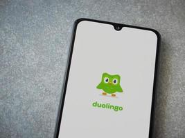 Duolingo - Language learning app launch screen with logo on the display of a black mobile smartphone on ceramic stone background photo