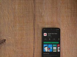 Pocket app play store page on the display of a black mobile smartphone on wooden background photo