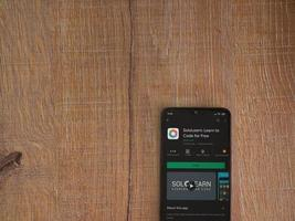 SoloLearn - Learning coding app play store page on the display of a black mobile smartphone on wooden background photo