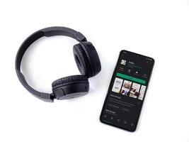 Black mobile smartphone with mako app play store page and wireless headphones on a white background photo