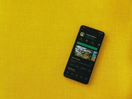 Hungry Dragon app play store page on the display of a black mobile smartphone on a yellow fabric background photo