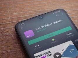 PAY app play store page on the display of a black mobile smartphone on wooden background photo