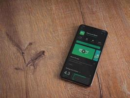 Bank Discount app play store page on the display of a black mobile smartphone on wooden background photo