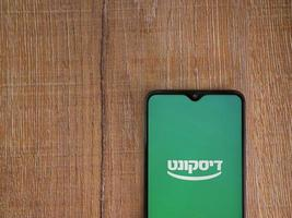 Bank Discount app launch screen with logo in hebrew text on the display of a black mobile smartphone on wooden background photo
