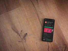 InShot - Video Editor and Movie Maker app play store page on the display of a black mobile smartphone on wooden background photo