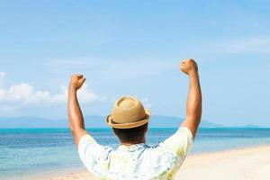 Happy young asian man on the tropical beach photo