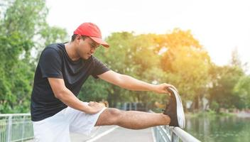Young fitness man runner stretching before run with copy space. photo