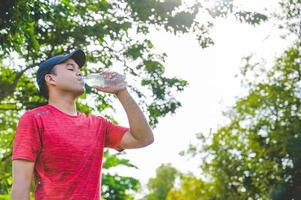 Young fitness man runner  drinking bottle of water. photo