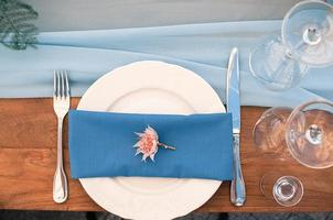 Wedding or event decoration table setup, blue napkin, outdoor photo