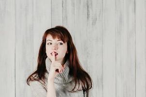 a sign of silence, or secret, finger on lips. Hush photo