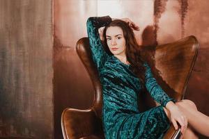 Hermosa joven sentada en un sillón de cuero marrón foto