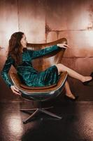 Chica guapa en vestido de terciopelo, sentada en un sillón de cuero marrón foto
