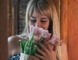 blurred image of a young blonde woman with flowers photo