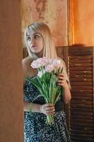 A blonde woman with bouquet of flowers by the window photo